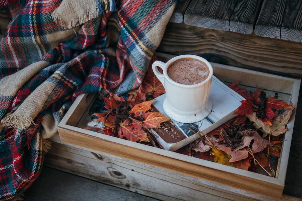 Hot coffee with a blanket and a book in a fall setting